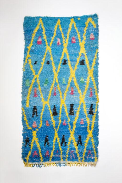 marokkansk-boucherouite-taepper-haendlavet-i-plastik-med-turkis-baggrund-og-gult-geometrisk-moenster